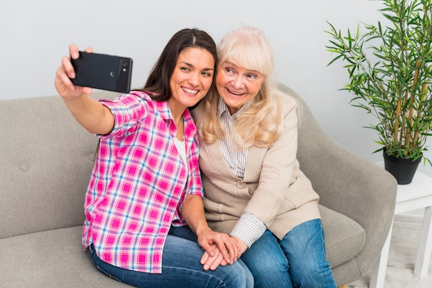 Ritratto sorridente di una donna senior e madre che prendono selfie sul telefono cellulare