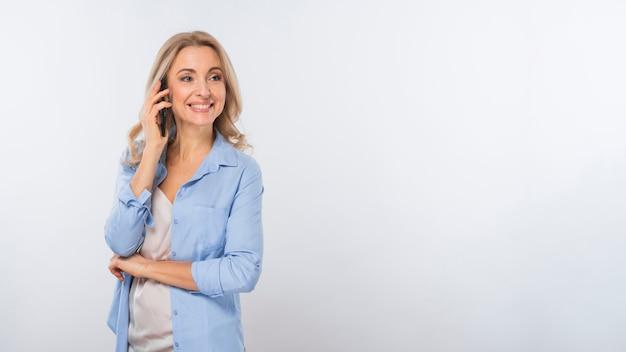 Ritratto sorridente di una giovane donna che parla sul telefono cellulare che sta contro il fondo bianco