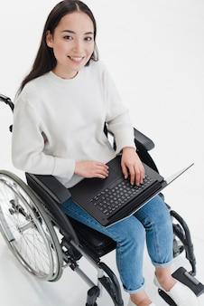 Ritratto sorridente di una giovane donna che si siede sulla sedia a rotelle con il computer portatile sul suo giro che guarda l'obbiettivo