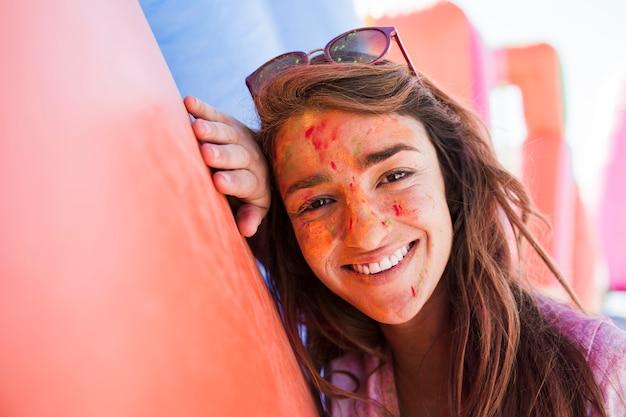 Ritratto sorridente di una giovane donna con i colori di holi su cipria che esamina macchina fotografica