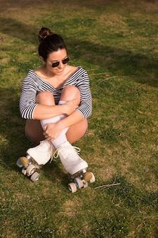 Ritratto sorridente di una giovane donna con le sue gambe attraversate che si siedono sull'erba verde