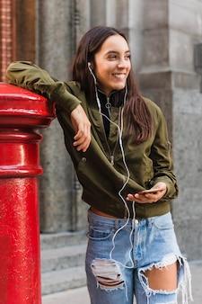 Ritratto sorridente di una musica d'ascolto della giovane donna sul telefono che sta sulla via