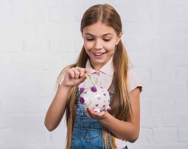 Ritratto sorridente di una ragazza che inserisce la nota di valuta nel porcellino salvadanaio bianco