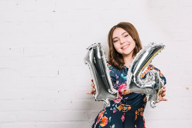 Ritratto sorridente di una ragazza che mostra pallone di stagnola di numero 14