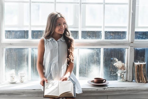 Ritratto sorridente di una ragazza che si siede sul davanzale della finestra che tiene libro che osserva via