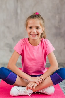 Ritratto sorridente di una ragazza che si siede sul tappeto rosa contro il muro di cemento grigio