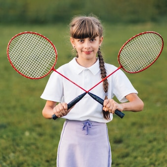Ritratto sorridente di una ragazza che tiene due badmintons attraversati