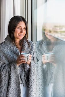 Ritratto sorridente riflettente della tazza di caffè della tenuta della donna a disposizione