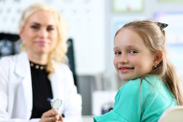 Ritratto sorridente sveglio della bambina con medico femminile nel fondo