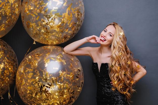 Ritratto splendida giovane donna giocosa con capelli biondi ricci lunghi divertendosi con grandi palloncini pieni di orpelli dorati su uno spazio nero