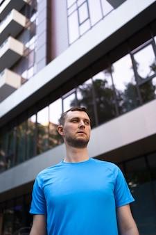 Ritratto sportivo dell'uomo sopra il fondo della costruzione di vetro