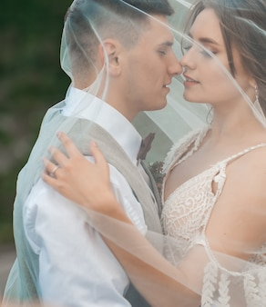 Ritratto sposi felici sposi avvolti in un velo che si abbraccia sullo sfondo del castello