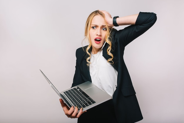 Ritratto stupito giovane donna bionda impegnata che lavora con il computer portatile. parlare al telefono, errore, umore sconvolto, essere in ritardo, impiegato, emozioni vere