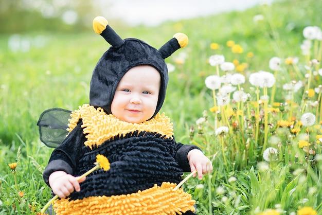 Ritratto sveglio e allegro del piccolo bambino che si siede in fiori che sbocciano del dente di leone in costume giallo dell'ape.