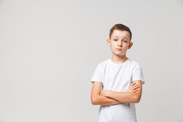 Ritratto triste del giovane ragazzo su fondo bianco con copyspace