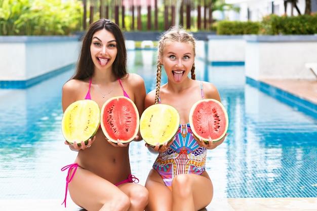 Ritratto tropicale di estate di due ragazze abbastanza giovani che hanno divertimento vicino alla piscina, tenendo due grandi angurie. mostra la lingua lunga