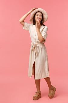Ritratto verticale a figura intera splendido, ragazza adorabile femminile che si diverte, cammina e gode della giornata di sole, indossa cappello e vestito, divertito guardando a destra e copre la bocca, rosa