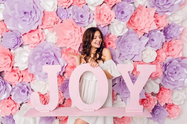 Ritratto verticale della ragazza bruna carina. si alza e tiene la parola di legno gioia che sorride ampiamente. ha uno sfondo rosa ricoperto di fiori
