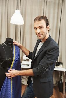 Ritratto verticale di giovane attraente designer maschio caucasico professionale in abito elegante, lavorando su una nuova collezione di abiti per seguire la sfilata di moda, controllando le dimensioni della scollatura usando il nastro di misurazione