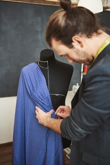 Ritratto verticale di giovane designer maschio di successo di bell'aspetto in giacca alla moda che osserva come appariranno le pieghe su questo tipo di tessuto sul manichino che si prepara per la sfilata di moda
