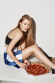 Ritratto verticale di giovane donna con i capelli biondi, seduto sul tavolo, con espressione soddisfatta andando a provare la pizza.