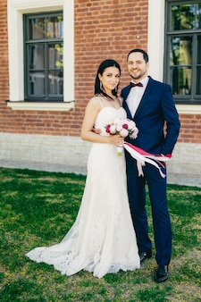 Ritratto verticale di sposi felici in piedi uno accanto all'altro, attendere gli ospiti, celebrare il loro matrimonio
