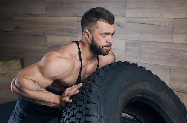 Ritratto vicino dell'uomo forte in canottiera nera e shorts grigio spazio con una barba che cerca di spingere una gomma in palestra