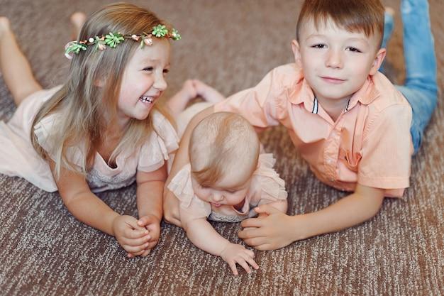Ritrovo insieme dei piccoli bambini e sorridere nello studio sul pavimento