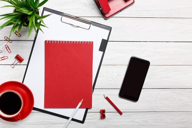 Riunione del flusso di lavoro della graffetta dell'orologio del caffè di mattina della tazza del blocco note della cartella rossa bianca dei bordi di scrivania