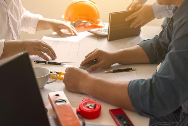 Riunione della gente di piano della costruzione di lavoro di squadra dell'architetto con i modelli.