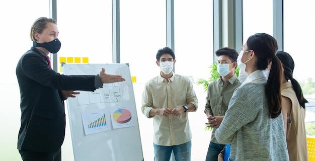 Riunione di brainstorming multirazziale di avvio di piccole imprese con cartone di carta ognuno indossa maschera