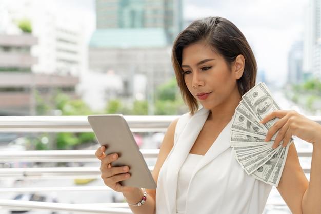 Riuscita bella giovane donna asiatica di affari che usando le fatture del dollaro americano dei soldi e dello smart phone a disposizione