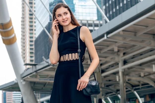 Riuscita donna di affari caucasica che parla sul telefono mentre camminando all'aperto.