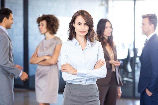 Riuscita donna di affari che sorride mentre i suoi colleghi che interagiscono a vicenda