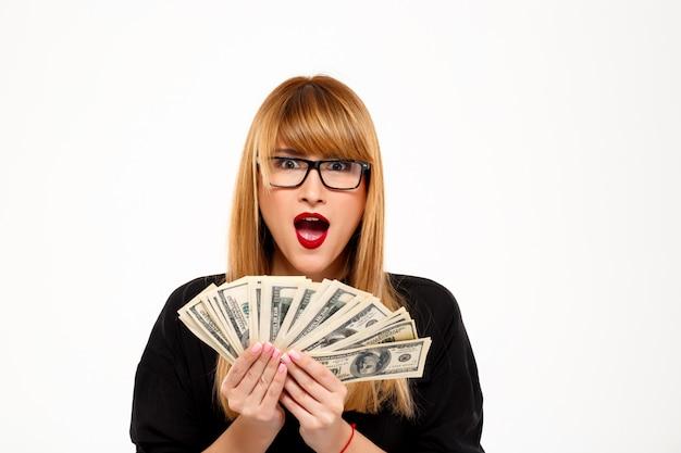 Riuscita donna di affari sorpresa in vetri che tengono soldi sopra la parete bianca
