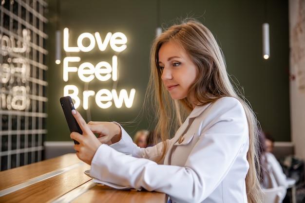Riuscita donna di affari sorridente del ritratto che si siede nel self-service che per mezzo dello smartphone