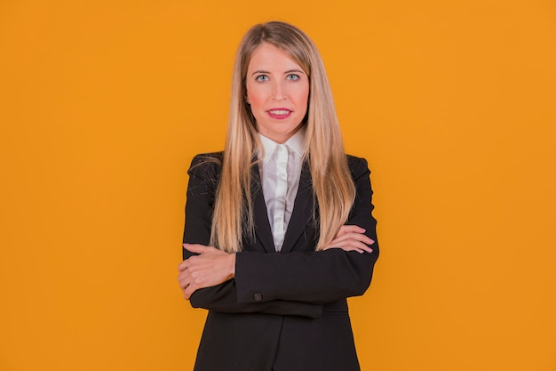 Riuscita giovane donna di affari che esamina macchina fotografica che si leva in piedi contro una priorità bassa arancione
