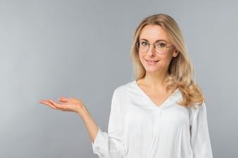 Riusciti occhiali d'uso della giovane donna di affari che presentano contro il contesto grigio