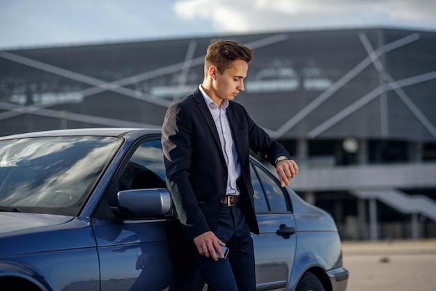 Riuscito giovane uomo d'affari attraente in un vestito che osserva sull'orologio vicino alla sua automobile