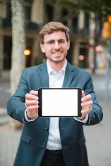 Riuscito giovane uomo d'affari che mostra compressa digitale con la visualizzazione di schermo bianca