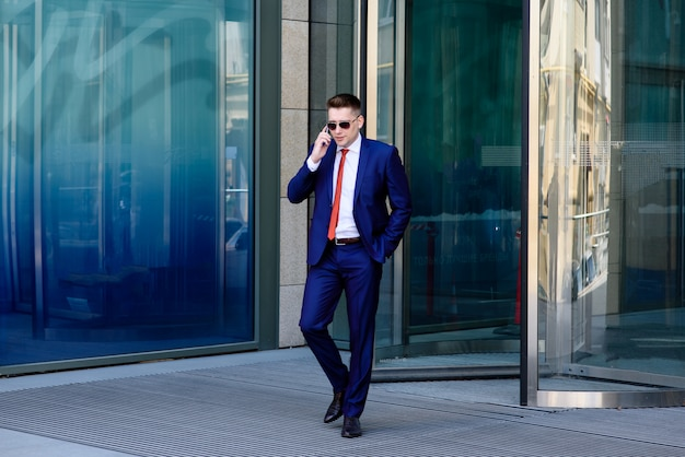 Riuscito uomo d'affari che parla sul telefono e sul sorridere.