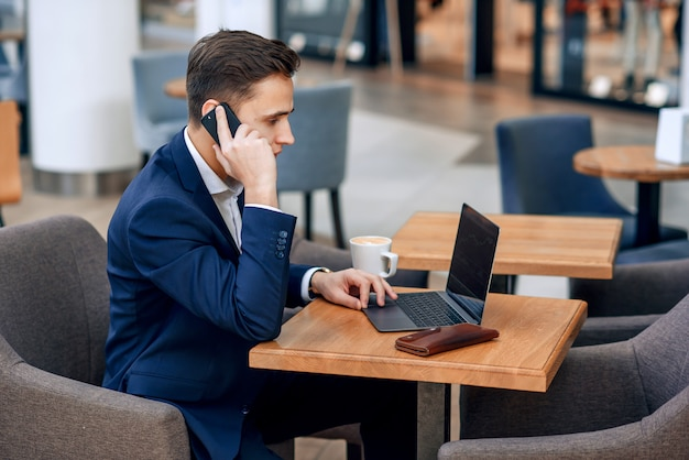 Riuscito uomo d'affari che parla sullo smartphone sul suo posto di lavoro con il computer portatile, il portafoglio e il taccuino
