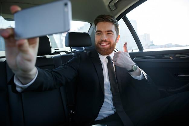 Riuscito uomo sorridente di affari che prende selfie