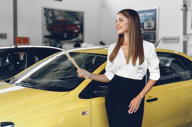 Rivenditore di auto femminile giovane attraente in piedi in showroom vicino a una nuova auto