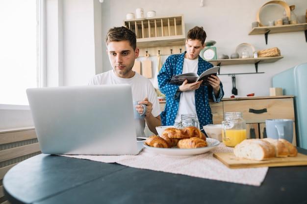 Rivista della lettura del giovane che sta dietro il suo amico che lavora al computer portatile con la prima colazione sul tavolo