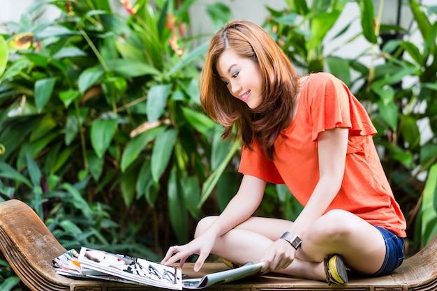Rivista di moda asiatica giovane della lettura della donna