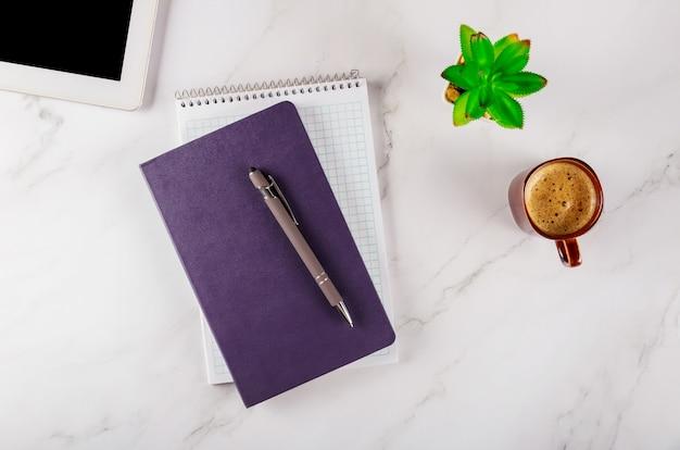Roba dell'ufficio con il blocco note, la compressa dei dispositivi digitali e la tazza di caffè, colpo di vista superiore.