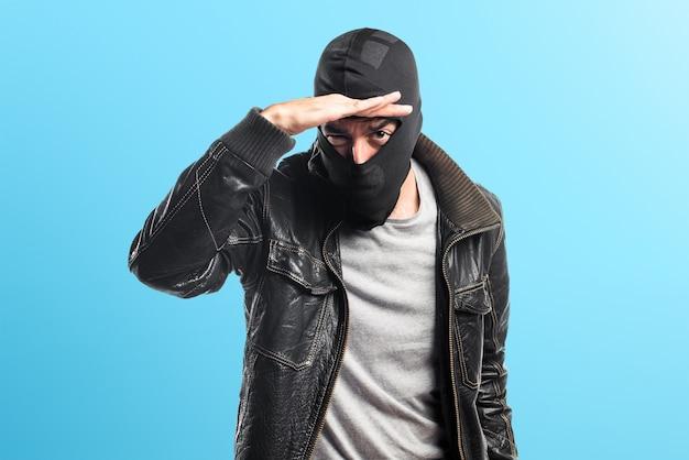 Robber mostrando qualcosa su sfondo colorato