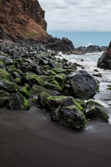 Rocce con muschio e mare agitato sulla spiaggia