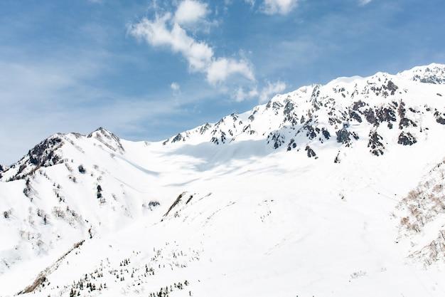Rocce sulla montagna innevata sotto il cielo blu